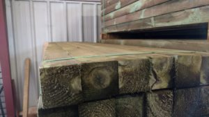 A neat stack of green treated posts in a lumber mill