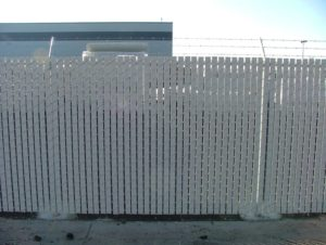 White plastic slats woven into a chain link fence to reduce visibility and provide wind protection