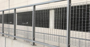 Aluminum bar grating panels protecting a parking structure from traffic