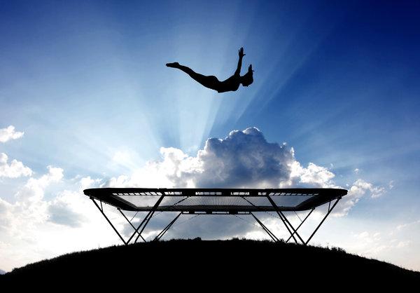 silhouette of female gymnast on trampoline in sky. Black Bedroom Furniture Sets. Home Design Ideas