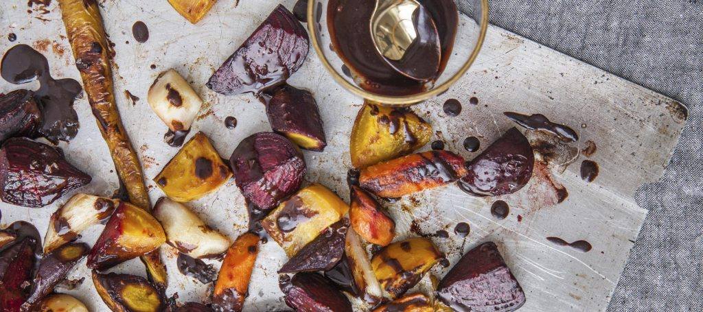 roasted vegetables topped with chocolate balsamic glaze on parchment paper