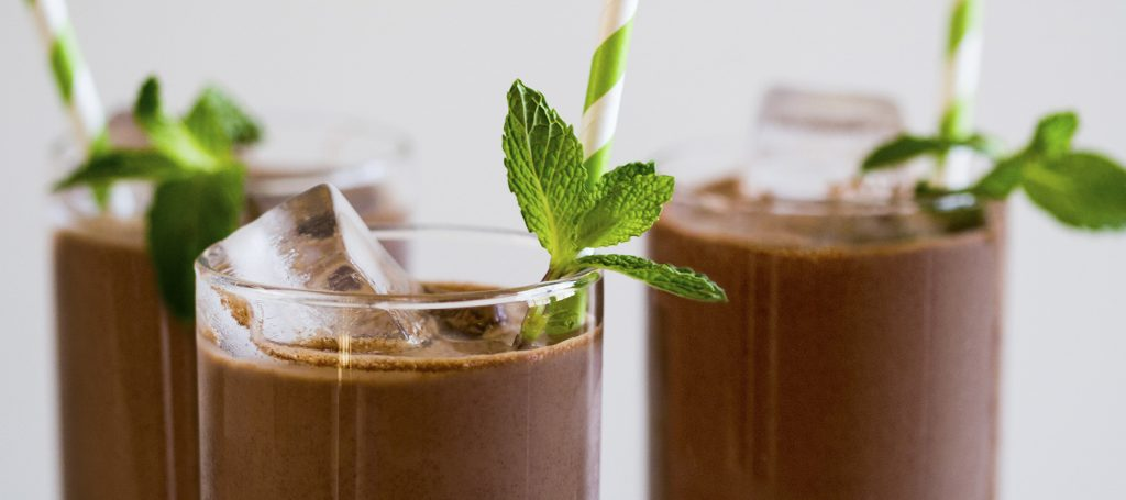 glasses of iced chocolate drinks with cardboard straws and a mint sprig garnish