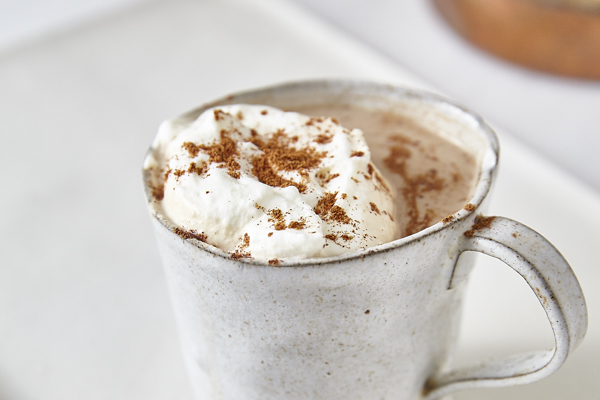 a spiced pumpkin latte in a tin mug on a white plate with whipped cream