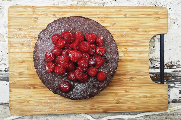 a whole chocolate zucchini cake on a wooden cutting board with raspberries on top