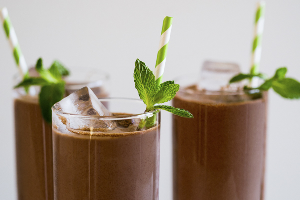 spiced chocolate drink in a glass with a mint garnish