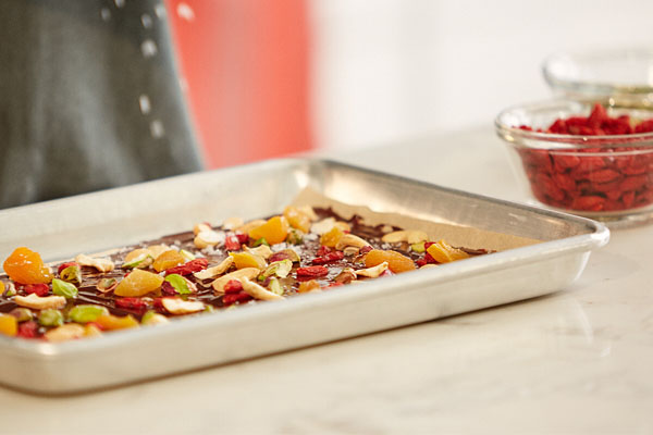 a close up image of chocolate bark with dried fruit in a baking tray, with a woman sprinkling salt on top