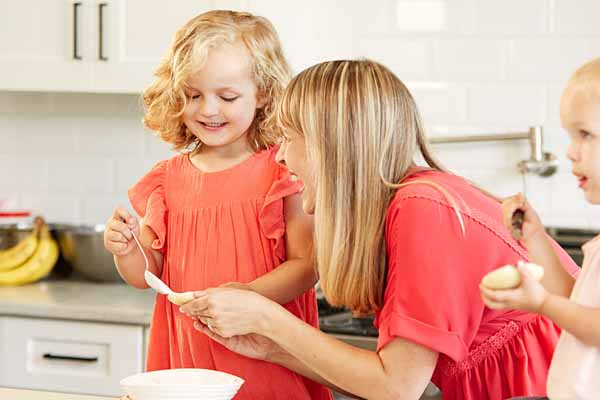 a woman and two toddler girls laughing in the kitchen baking cookies