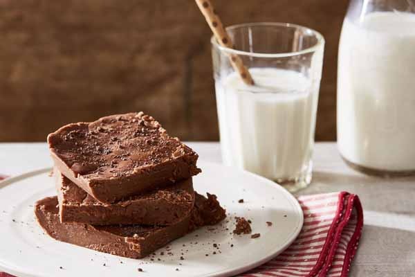 a plate of historic chocolate fudge with a glass of milk on a red checkered cloth