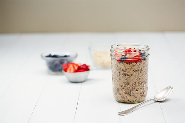 Chocolate overnight oats in a mason jar on a white wooden tabletop