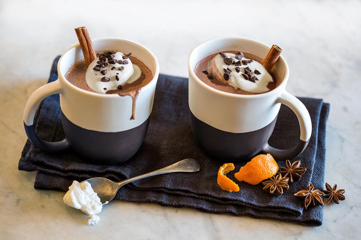 two mugs of american heritage chocolate gourmet hot chocolate on a tea towel with orange peel and cinnamon