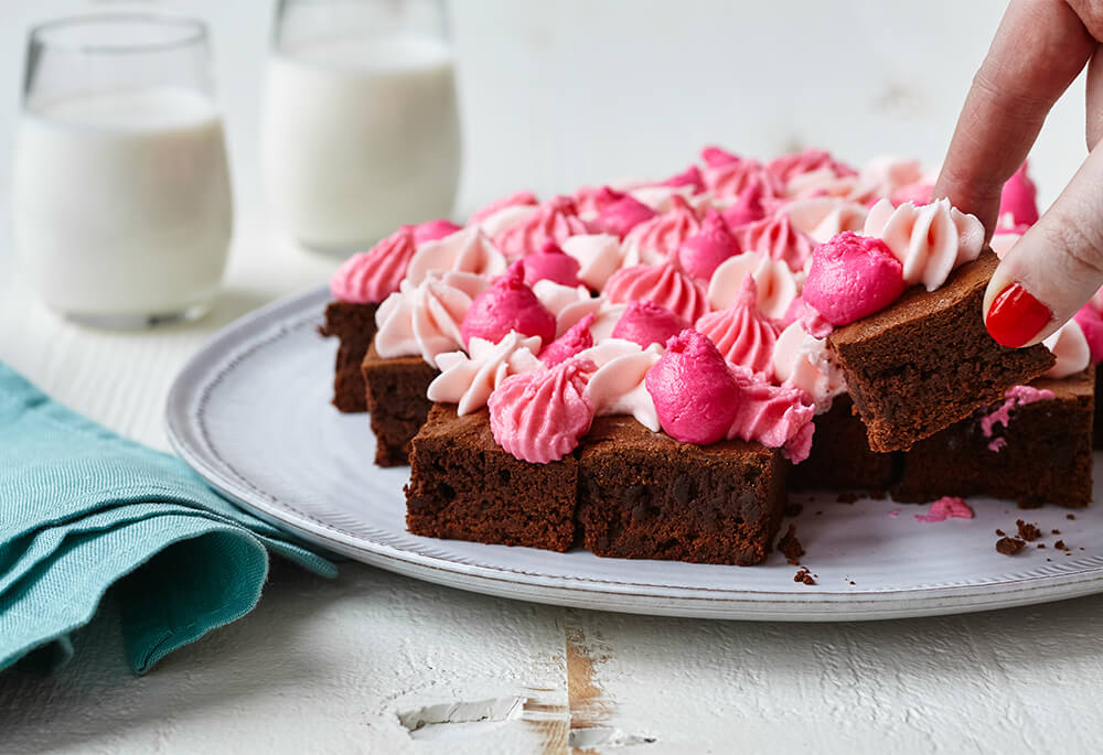 Pink and red vanilla buttercream frosting on chocolate brownies, set up on a white plate