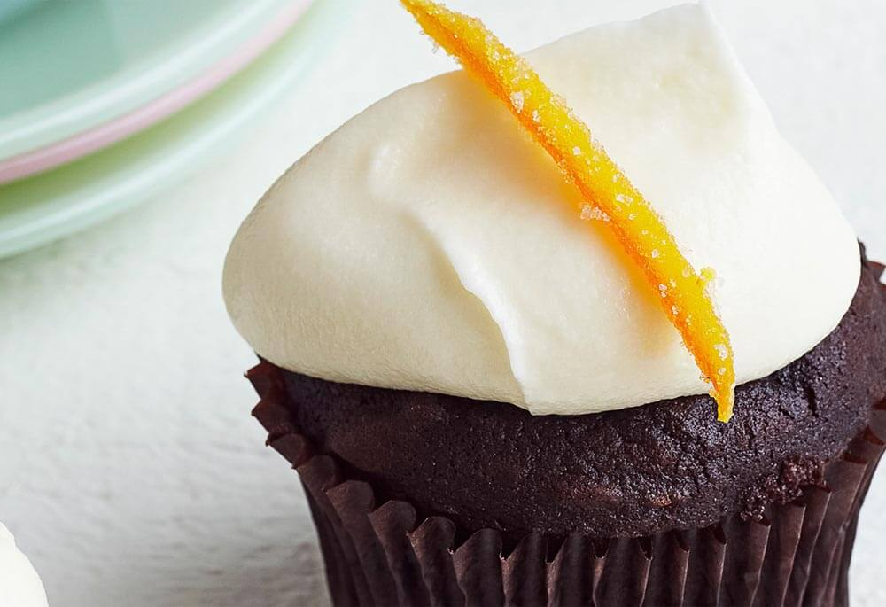 AMERICAN HERITAGE Chocolate cupcake with cream cheese frosting and a candied orange garnish