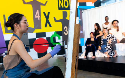 """Leena Cho painting the group portrait of Mei Ann Teo, Sarah Shin, Diana Oh, Cassandre """"Jolie LaVie"""" Charles, and Ian Askew at The Artist in Their Element."""