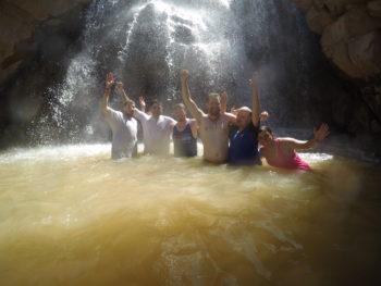 RRAFT participants enjoy a dip in a waterfall. | Dan Omasta