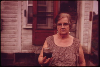 Mary Workman holds a jar of undrinkable water that comes from her well, and has filed a damage suit against the Hanna Coal Company, October 1973. | Erik Calonius / EPA