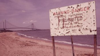 Warning of polluted water at Staten Island Beach, Verrazano-Narrows Bridge in the background, June 1973. | Arthur Tress/EPA