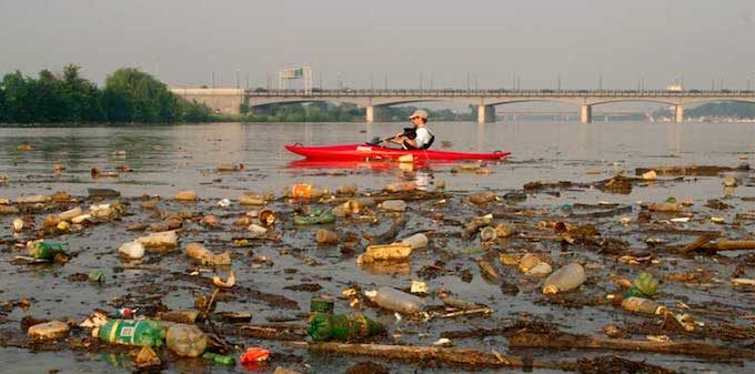Kayaking around trash in the Anacostia River. | Photo: National Geographic/Skip Brown