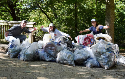 Volunteers pose with trash at a National River Cleanup event on Teddy Roosevelt Island, DC. | Rebecca Long
