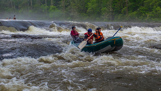 Melissa Martinez, Mike Huffman and local-legend Bruce Hare power through Dick's Creek Ledge on a high-water Section 3 of the Chattooga. | Credit: Jack Henderson