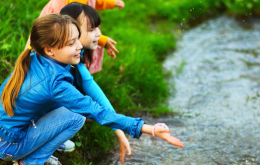 Kids playing along a stream