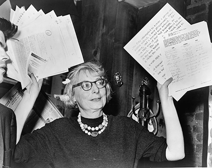 Stanziola, Phil, photographer. Mrs. Jane Jacobs, chairman of the Comm. to save the West Village holds up documentary evidence at press conference at Lions Head Restaurant at Hudson & Charles Sts / World Telegram & Sun photo by Phil Stanziola. New York, 1961. December 5. Photograph. Retrieved from the Library of Congress.