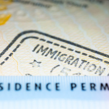 Immigration concept image. Residence permit card over immigration stamp on UK visa in passport