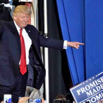 """HARRISBURG, PA - APRIL 29, 2017: President Donald Trump walks does a """"double point"""" to his supporters before a speech marking 100 days in office. Held at The Farm Show Complex and Expo Center. - Image"""