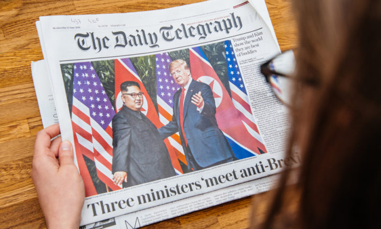 PARIS, FRANCE - JUNE 13, 2018: Woman reading The Daily Telegrpah newspaper in the office showing on cover U.S. President Donald Trump meeting North Korean leader Kim Jong-un in Singapore