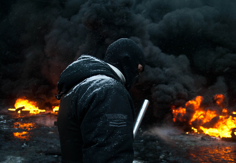 Kiev, Ukraine - 19 January, 2014: unknown radical protest near the burning barricades during the revolution in Ukraine