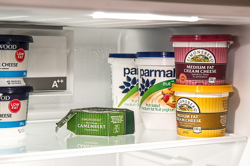 Multiple food items on a glass refrigerator shelf