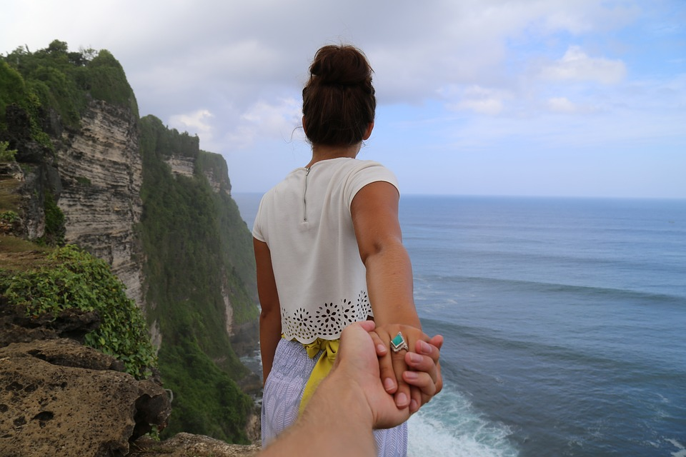 A woman and man holding hands by the ocean