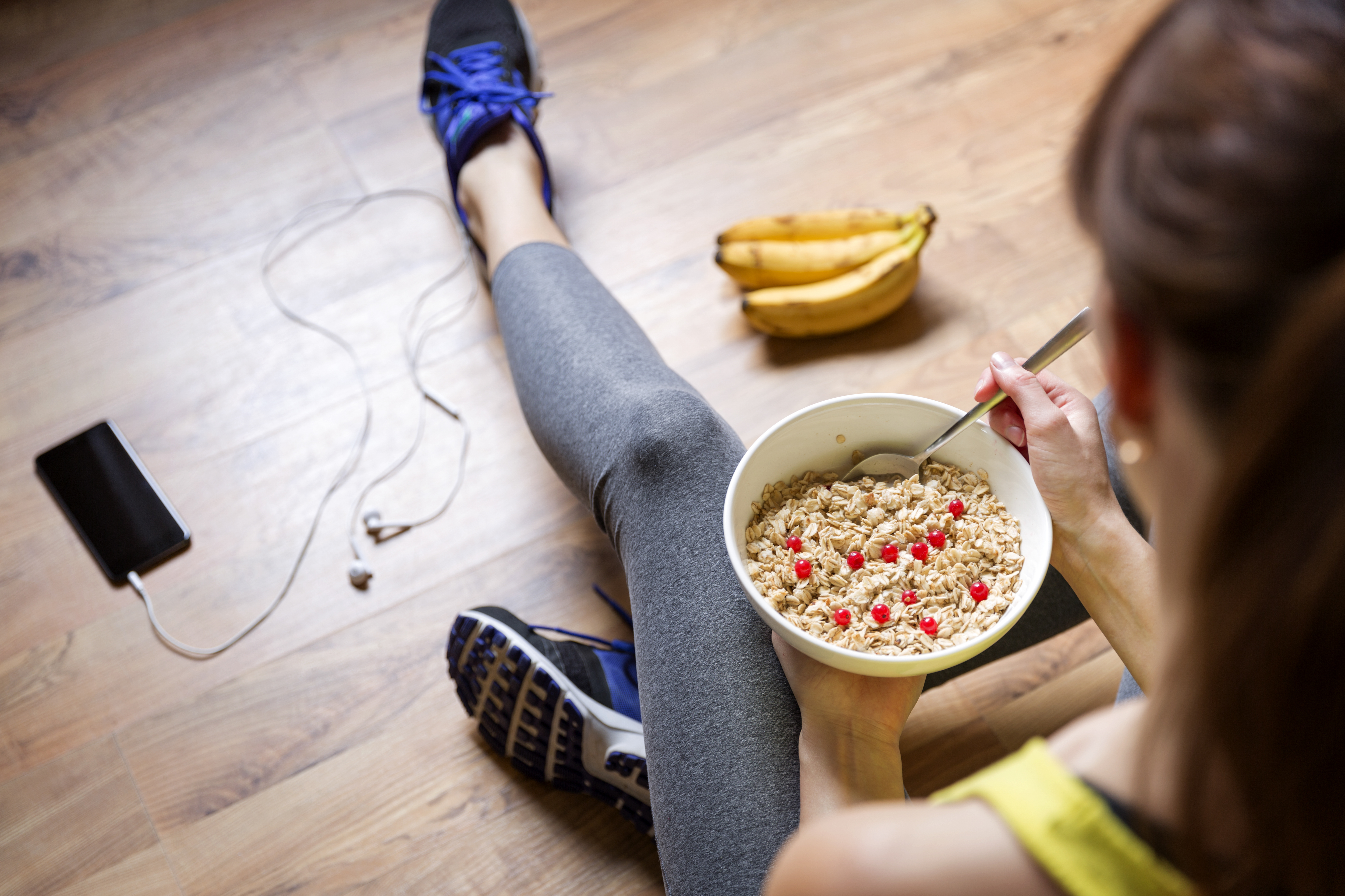 A woman eating oatmeal with berries after a workout