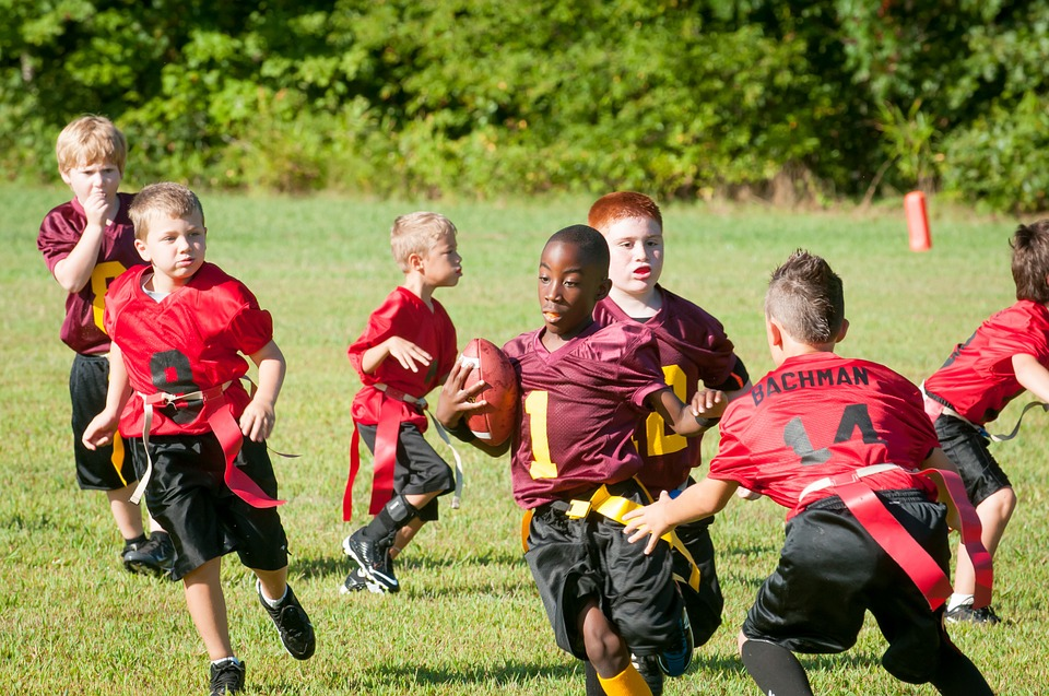 A group of children playing flag football