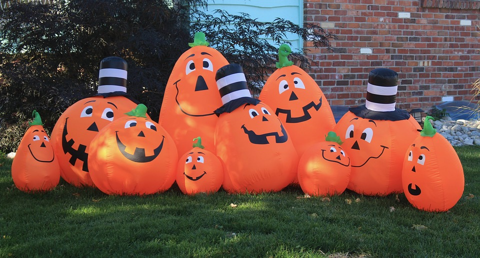 Pumpkin balloons with faces on a lawn