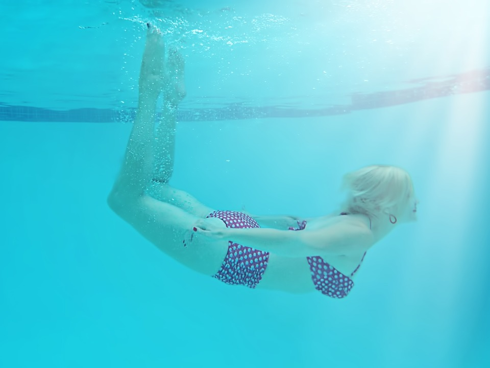 A woman underwater in a pool