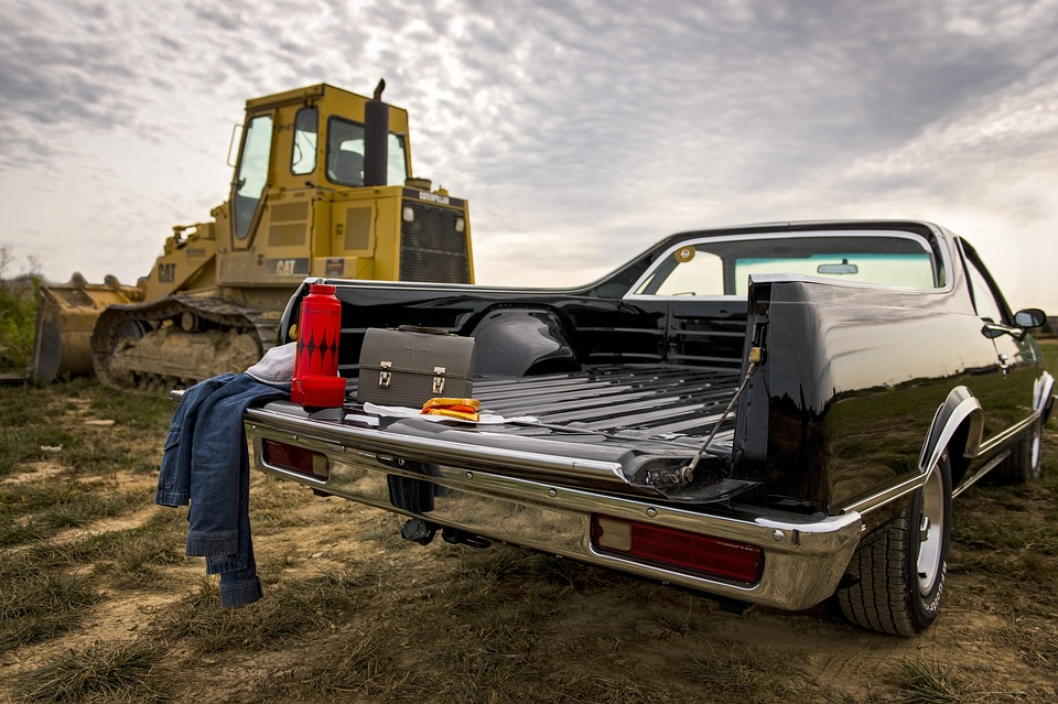A black car with work supplies in the bed parked in front of a bulldozer