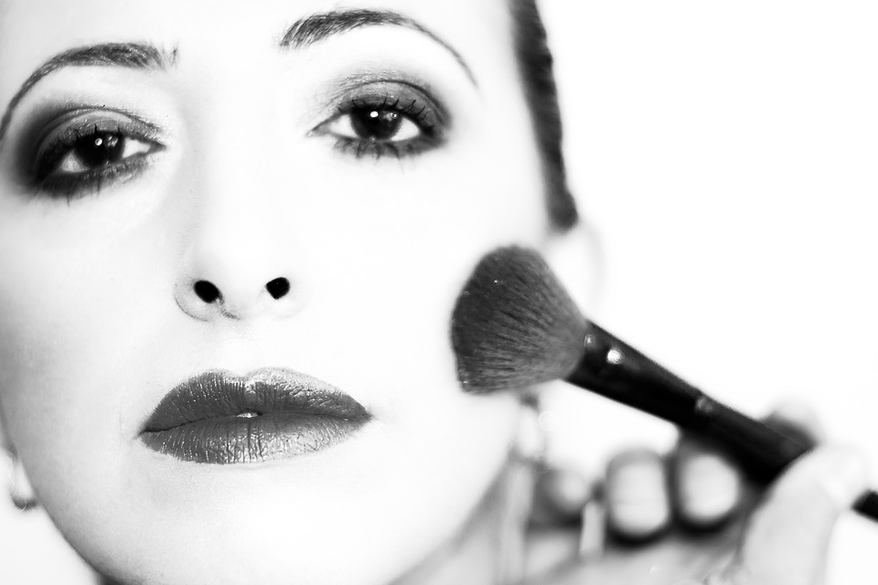 A black and white photo of a woman applying makeup