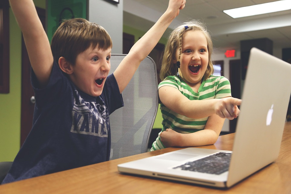 Two children playing a game on a laptop