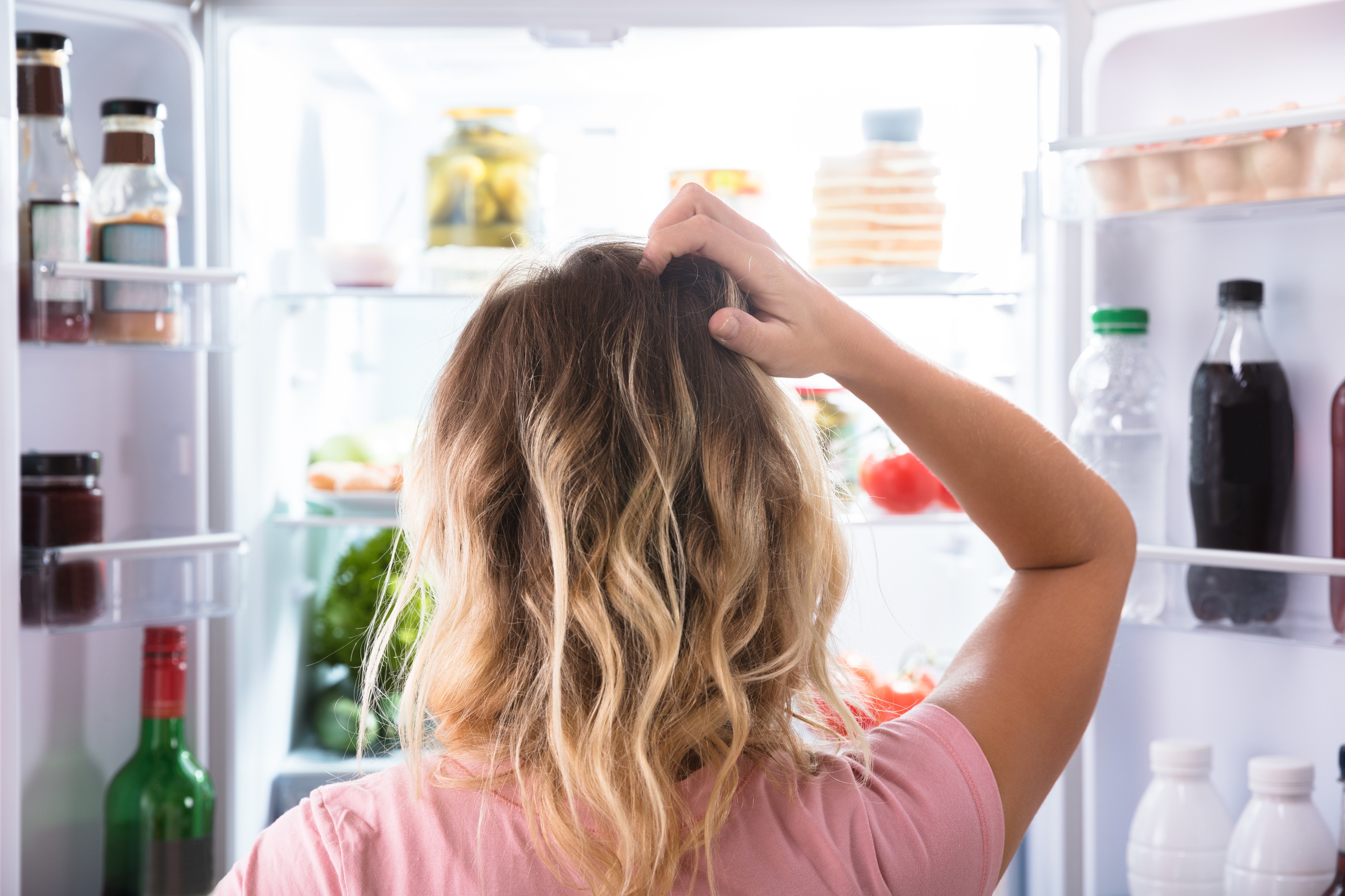A person looking into a refrigerator full of food