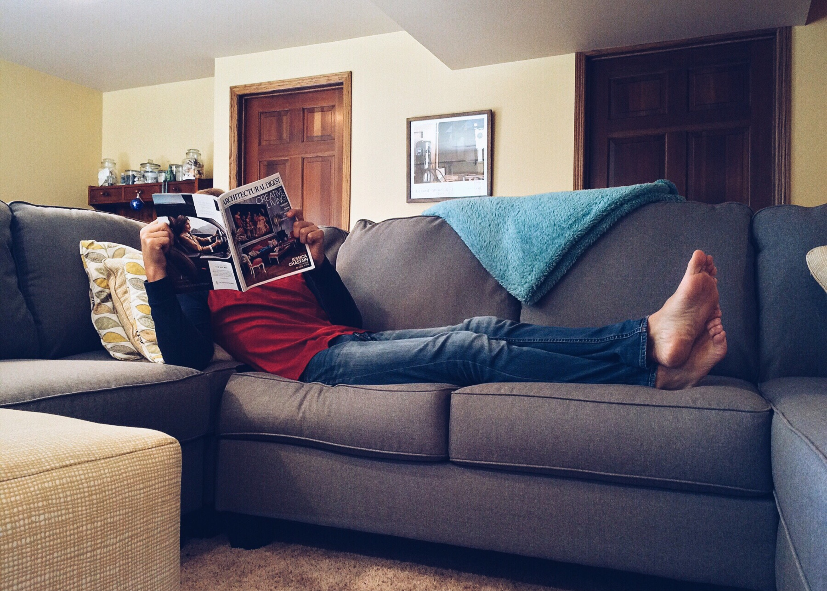 A person lounging on a gray couch reading a magazine