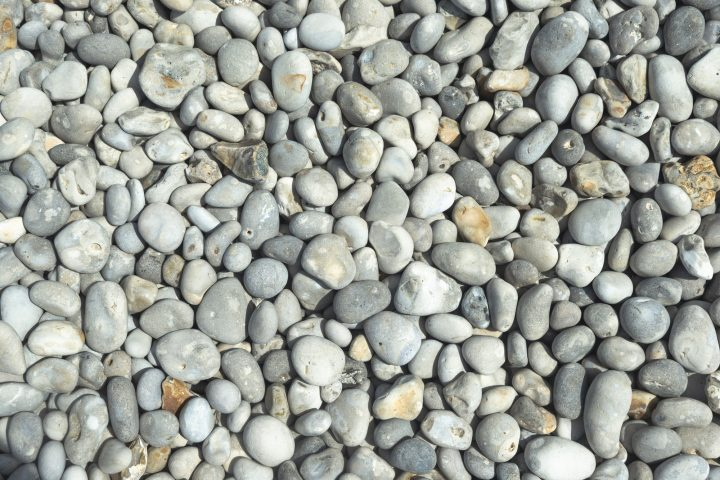 All rounded tiny pebbles from beach a natural summer background smooth polished pebble stones