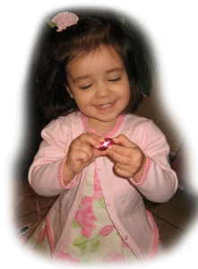 Little girl gleefully unwrapping a chocolate egg