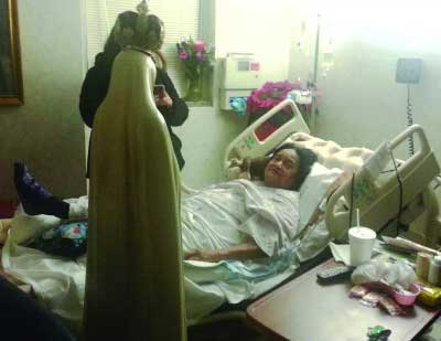 Woman in a hospital bed with statue of Our Lady used in Fatima Home Visits