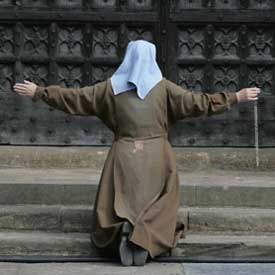 Nun kneeling on stairs praying the rosary with arms outstretched