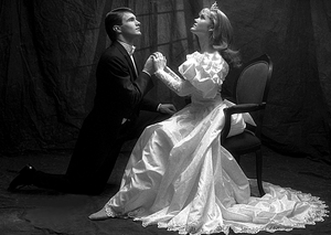 Black and white photo. Young man in white-tie attire is on one knee before a young woman sitting on a chair in an old fashioned formal gown or wedding dress, with a long skirt fanned around her, large puffy sleeves, and a crown, with hair down. They are holding hands, and both are looking upwards with a dreamy expression.