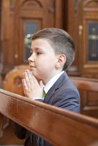 Image of a little boy praying in church