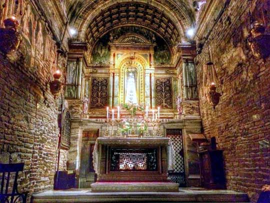 The interior of the Holy House of Loreto - the walls are simple brick. An altar is at one end.
