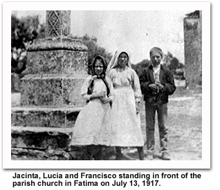 Jacinta, Lucia, and Francisco standing in front of the parish church in Fatima on July 13, 1917.