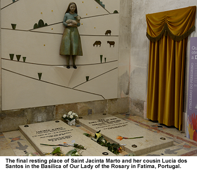 Photo of the final resting place of Jacinta Marto and her cousin Lucia dos Santos in the Basilica of Our Lady of the Rosary in Fatima, Portugal.  There is a statue of a young girl holding a lamb on the wall, and flowers over the tombs.