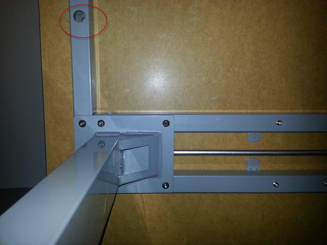wood screw underneath the manual crank desk frame
